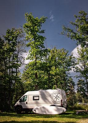schweden weißer camper im wald standup paddel angelehnt blauer himmel