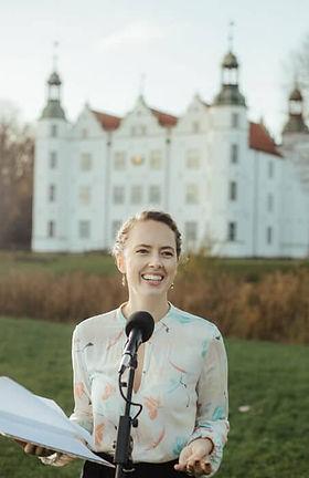 Freie rednerin für freie Trauung in Hamburg steht vor dem Schloss Ahrensburg an einem Mikrofon und haellt eine Zermemonie.