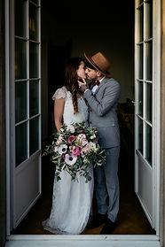 bodentiefes fenster mit brautpaar in einer villa bei zürich. braut und bräutigam küssen sich  Hochzeitsreportage von momentum by Fotografie Philipp Dietrich. Hochzeitsfotograf aus Hamburg.