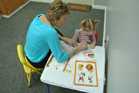 Speech Therapist helping child with speech by coloring