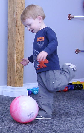 Child in clinic kicking ball