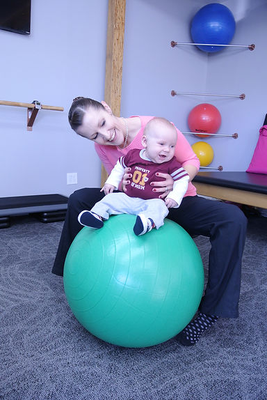 Doctor working with baby on ball