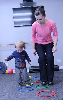 Doctor helping child with balance and hand eye coordination