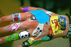 Hand covered in colorful bandaids