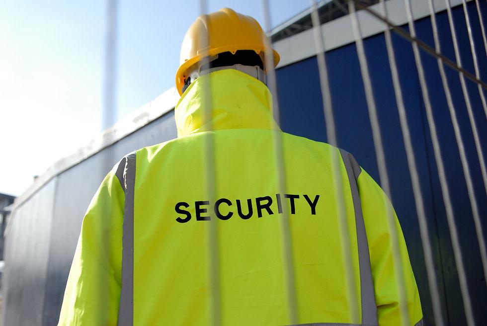 Security guard behind metal fence. .jpg