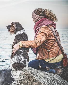 Eine Frau hat ihren Hund im Arm und blickt gemeinsam mit der Hündin in die Ferne