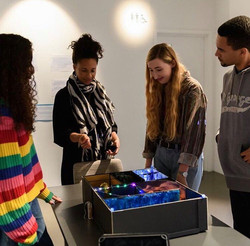 4 people standing around a table looking at a model box