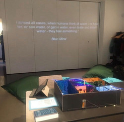 A projected quote on a wall. A model box on a table.