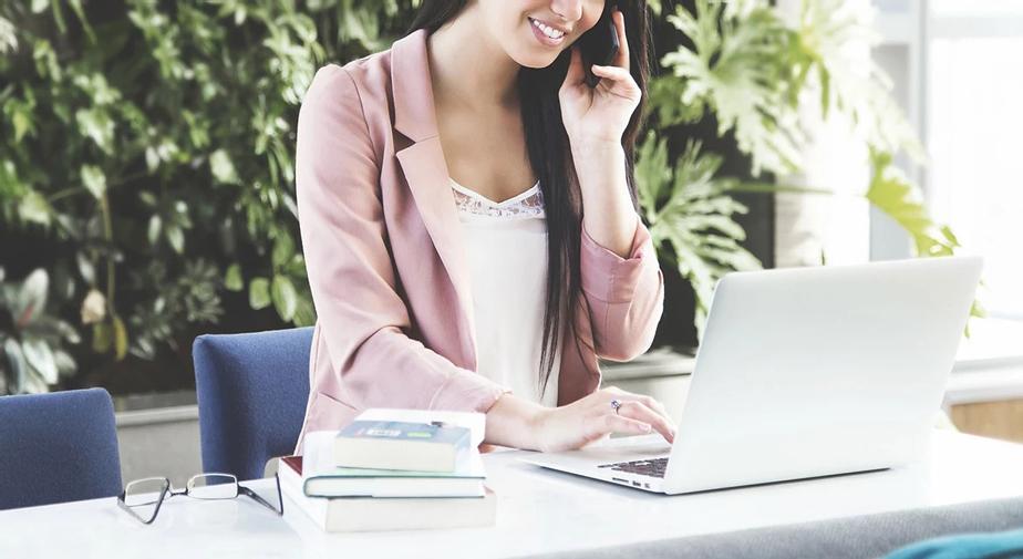 Mujer emprendedora con telefono móvil y computador portátil