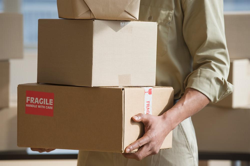 Mensajero cargando tres paquetes de envio