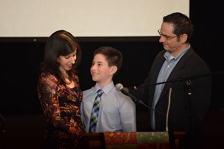 Proud parents smile their so during his Bar Mitzvah. Folkshul offers an alternative Bar Mitzvah and Bat Mitzvah program.