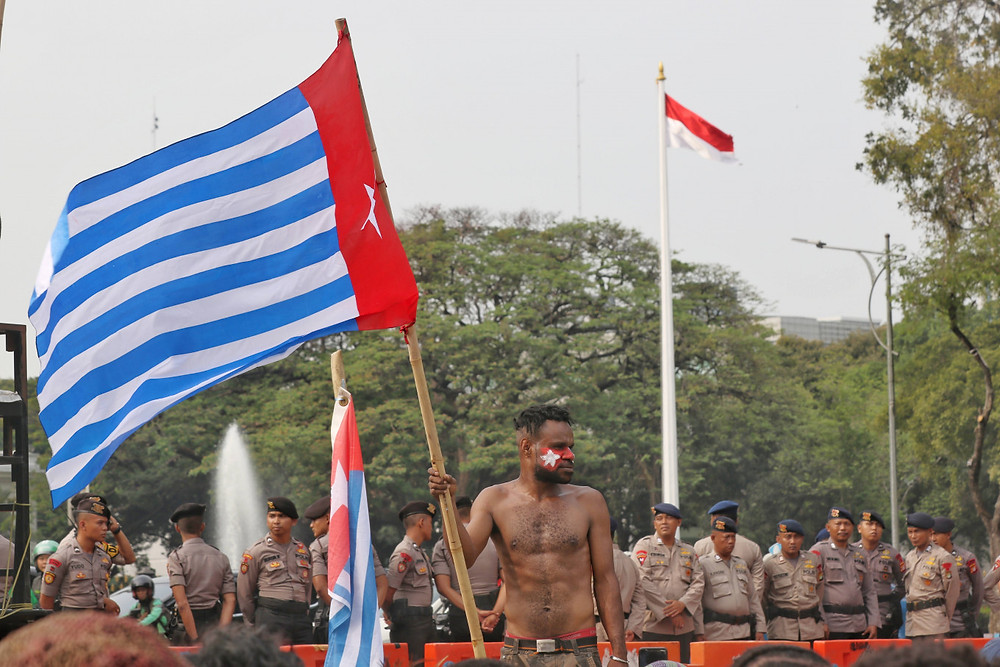 A member of the Papuan Student Alliance (AMP) holds a Bintang Kejora (Morning Star) flag as he stands in front of dozens of police officers during a rally at the State Palace in Central Jakarta. (JP/Dhoni Setiawan)