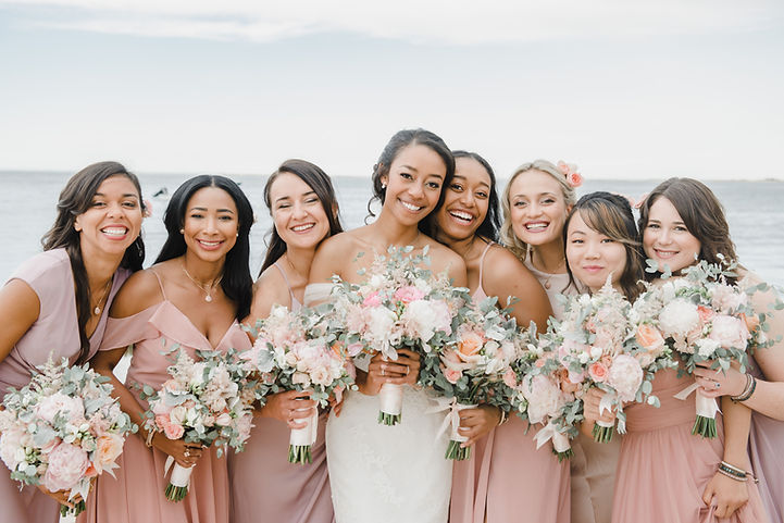 several bridesmaids gathered around the beautiful bride holding their bouquets. Makep done by Julia Rose Bride
