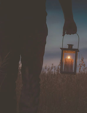 silhouette photo of man carrying candle lantern with lighted candle_edited_edited.jpg