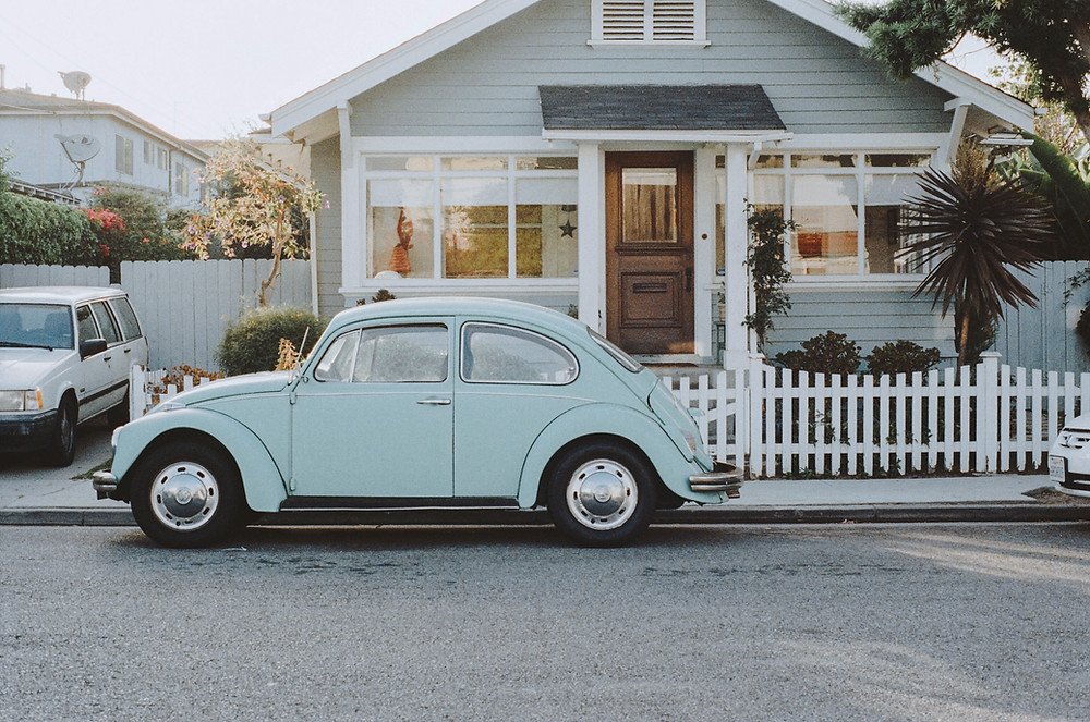 A Volkswagon Beetle parked by the curb outside a house.