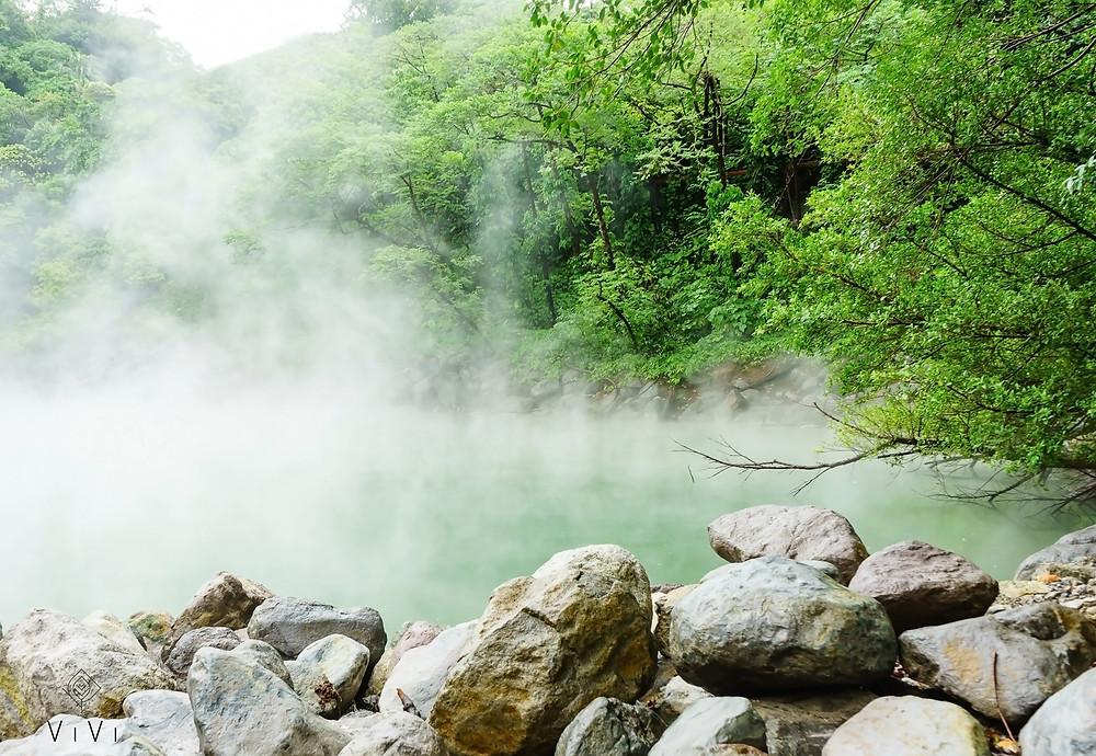 Lago termale con vapore caldo alberi e rocce