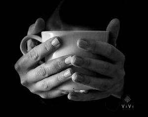 Mani che tengono tazza di te caldo dumante