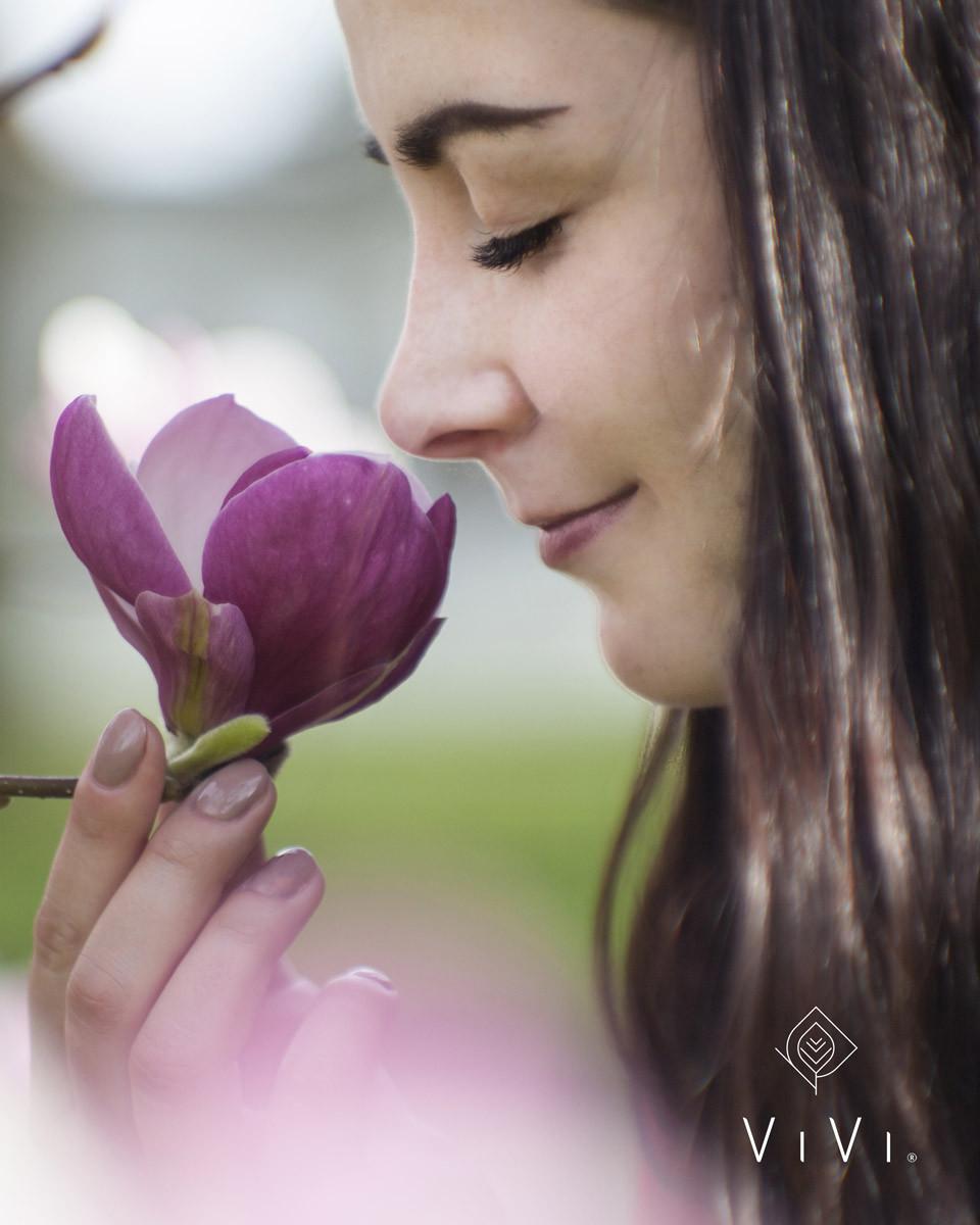Donna che annusa fiore violetto magnolia