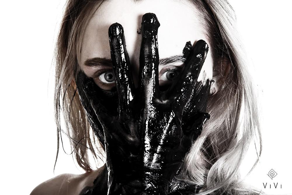 donna mette mano sporca di petrolio sul viso