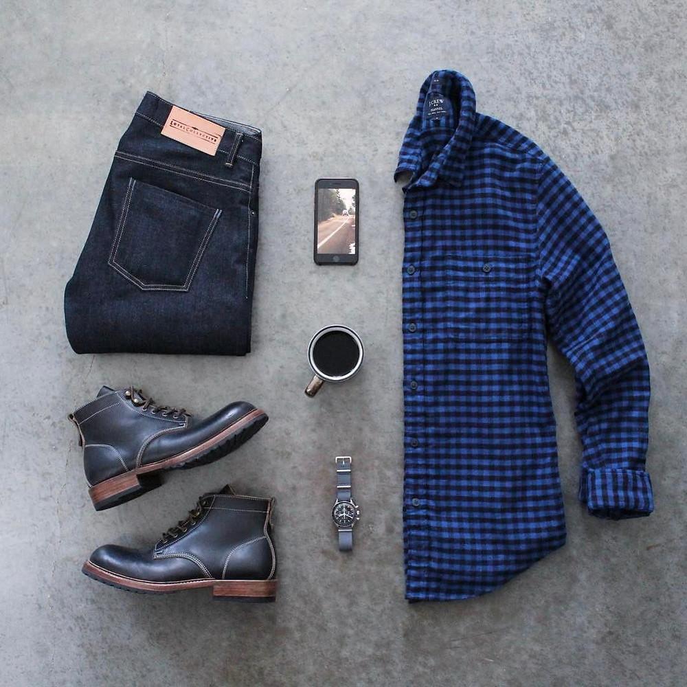 look masculino com blusa azul xadrez, bota de couro, calça jeans, e relogio.