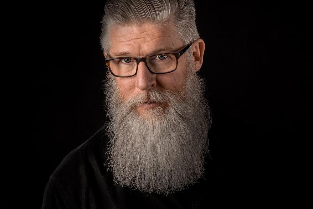 homem velho com barba grandde branca e cabelos brancos com óculos olhando pra frente
