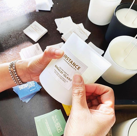 putting labels on each candle pouring soy wax on each container handmade product