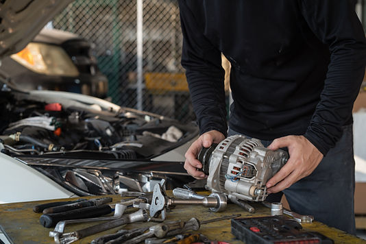 Mechanic man holding alternator of the c