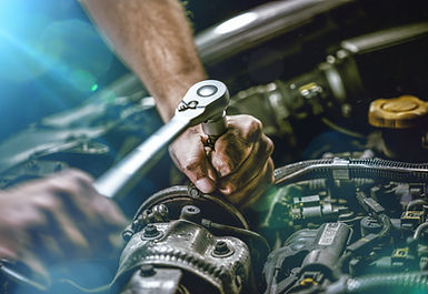 Auto mechanic working on car engine in m