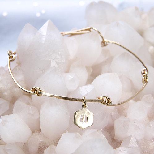 Golden bracelet with monogram charm