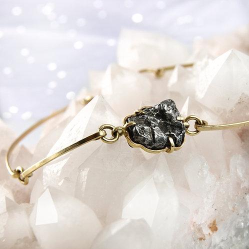 Golden bracelet with meteorite piece