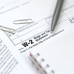 The pen and notebook on the tax form W-2