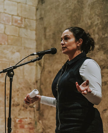 Picture of the poet and spoken word artist Chloe Jacquet performing at Blackfriars Priory in Gloucester. She wears a denim jumpsuit and is standing with her arms open, speaking into a microphone, against a bare yellow brick background. In her right hand is a spray can.