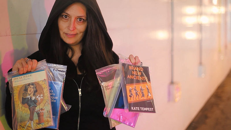 Picture of the poet and spoken word artist Chloe Jacquet in a subway wearing a black hoodie, looking to camera and holding up poetry books in plastic baggies. Image taken from the video of the poem The Dealer.