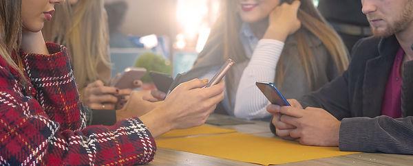 friends-sitting-in-bar-and-using-smartphone-NAQT5WU.jpg
