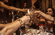 People raising glasses to cheers  -takes you to our event page