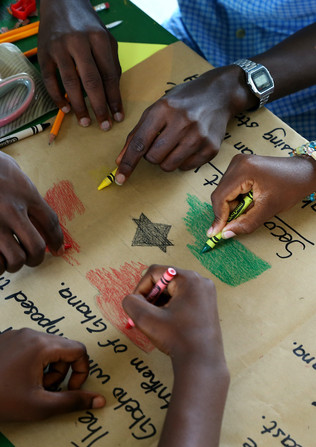 School kids drawing the Ghana Flag