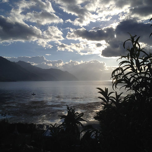 Photo of Lake Atitlan, Guatemala, with clouds in the sky and a single canoe in the distance