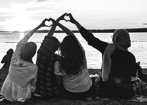 four people sitting on shore forming hearts with their hands during golden hour_edited.jpg