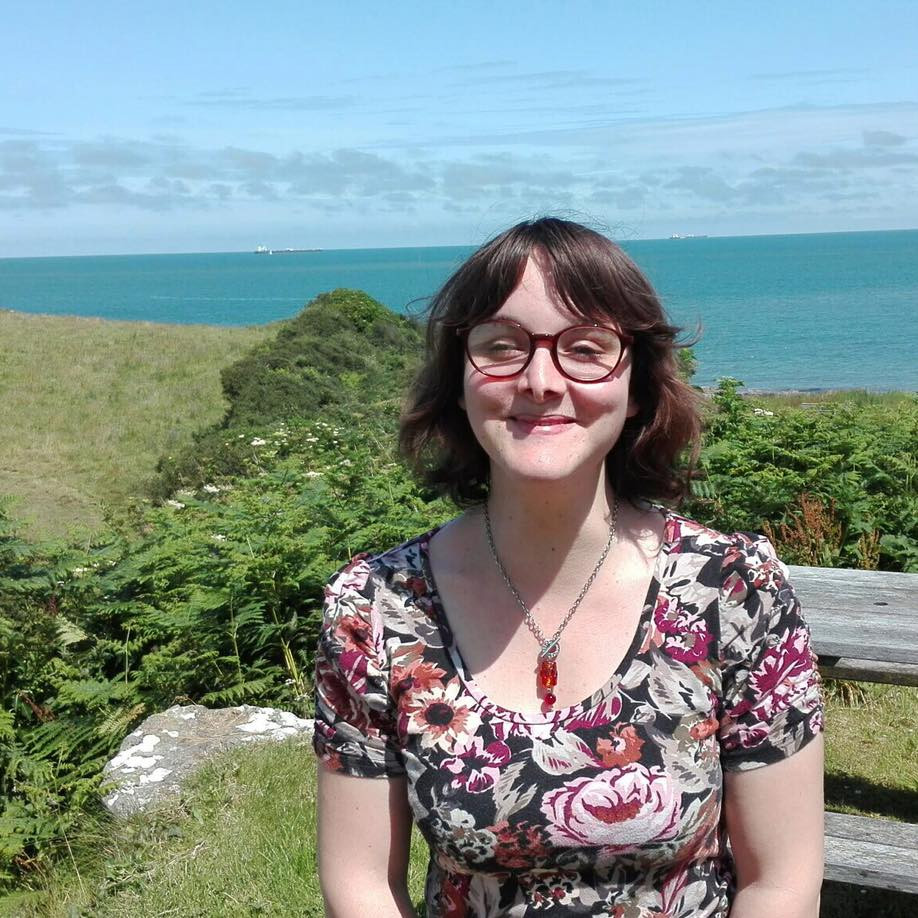 A picture of Claire. She has fair skin and dark-brown hair. She is wearing a red pair of glasses and she is smiling at the camera. The sea and some greenery can be seen in the background.