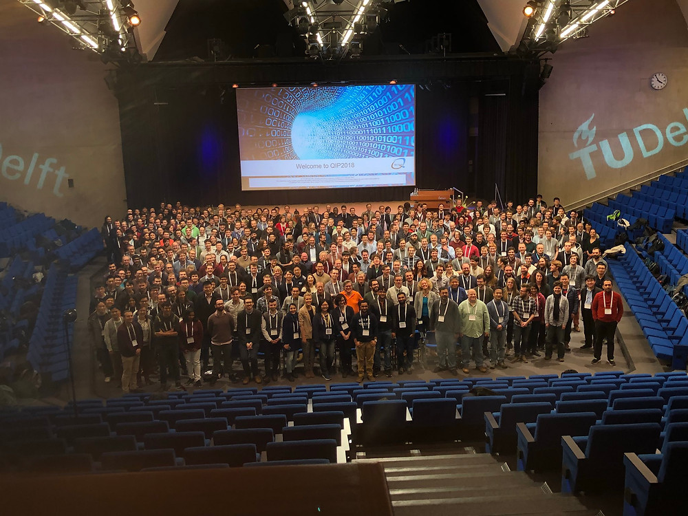 A photo taken of around 500 people who attended QIP2018. They are standing in the middle of an auditorium, looking up at the camera.