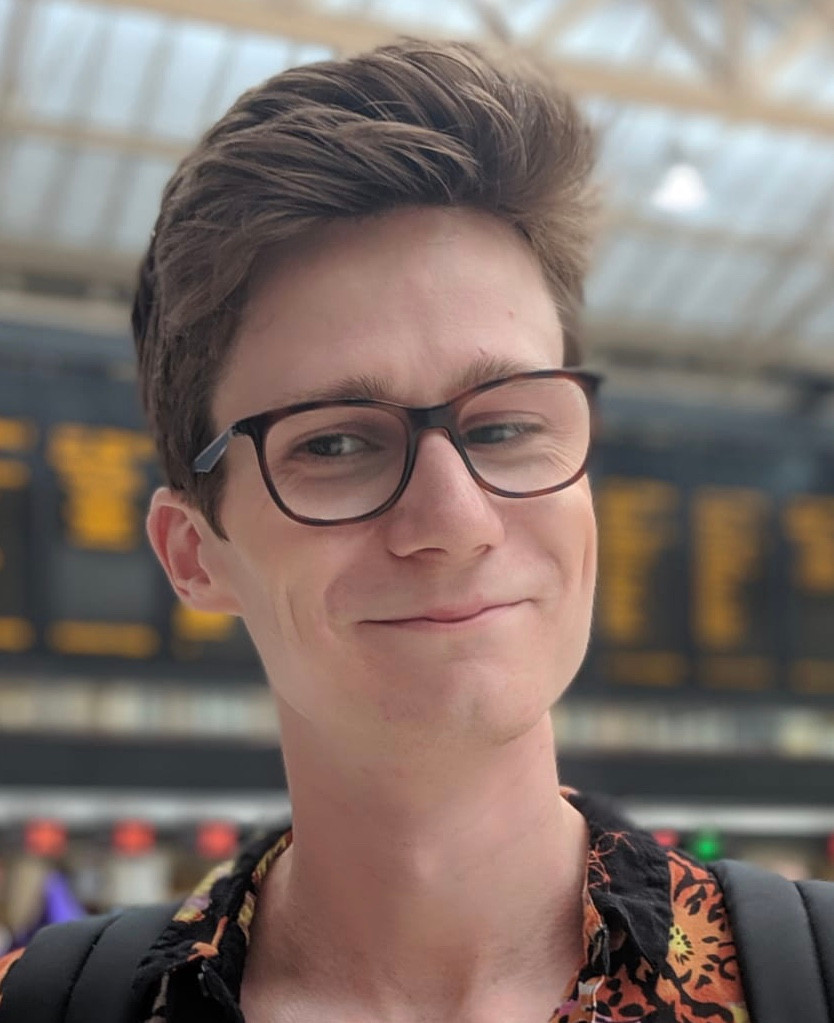 A photo of Robbie, who is similar at the camera. He has light skin and short, brown hair, and is wearing glasses with black frames. The background of the image is a train station.