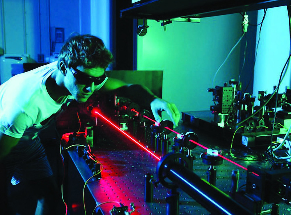 A PhD student with protective glasses is aligning a lens on an optical table. A red laser goes through a number of lenses. There are more optics devices in the background and the room is bathed in a green light.
