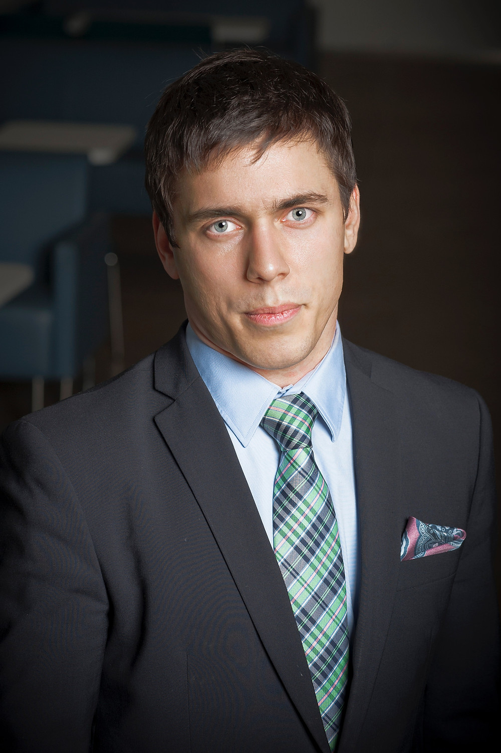 A picture of Dennis. He is wearing a suit and tie, has short, dark hair and is looking into the camera with a bit of a smile.
