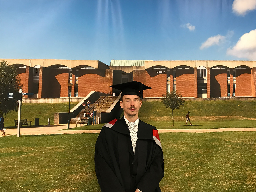 A picture of Dániel at his graduation. He is wearing a black cap and robe and is standing on a field in front of a red-brick university building. He has brown hair and beard and is smiling at the camera.