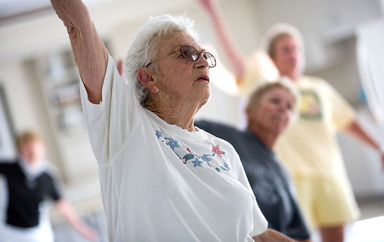 An elderly woman stretching in an exercise class