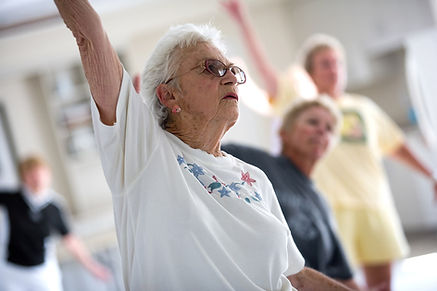 Close up of white haired woman in white shirt in seniors exercise yoga class