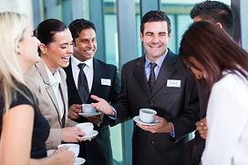 funny businessman telling a joke during conference coffee break.jpg