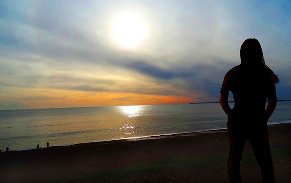Writer DJ Bowman-Smith on a beach at sunset
