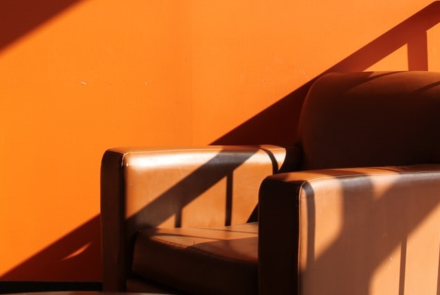 brown-leather-chair-orange-wall