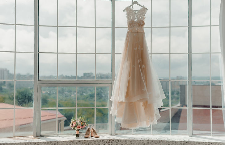 The bride's dress hangs on the window_ed